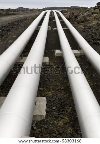 Pipes carrying geothermal energy across a lava field in Iceland - stock photo