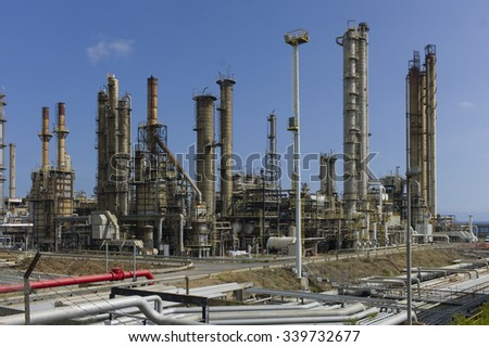Pipes, tubes and heavy industry machinery on an industrial area at a blue sky - stock photo