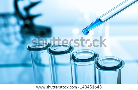 pipette and test tube on blue background - stock photo
