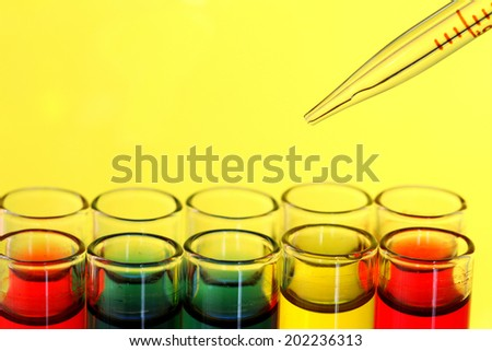 pipette and test tube on yellow background - stock photo