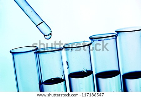 Pipette and test tubes in blue tone. - stock photo