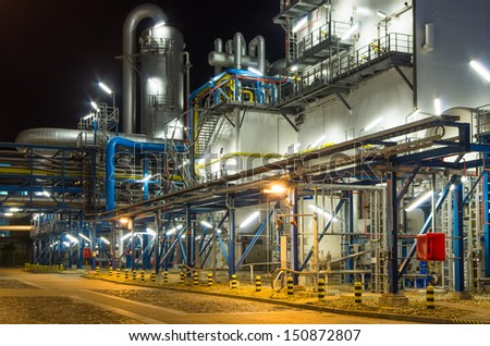 piping system inside of industrial plant at night - stock photo