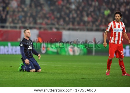 PIRAEUS GREECE -FEB. 25 Olympiakos' Alejandro Dominguez (R) and Wayne Rooney(L) of Manchester United during match: Olympiacos FC and Manchester United (2-0) at Karaiskakis Stadium on February 25 2014  - stock photo