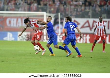 Piraeus,Greece Oct. 22, 2014. Olympiakos' Alejandro Dominguez, fights for the ball, next to Arturo Vital and Andrea Pirlo during the soccer match between Olympiakos and Juventus (1-0)   - stock photo