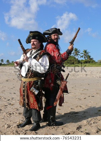 Pirate Duel. Two costumed pirates with pistols standing back to back on the beach. - stock photo