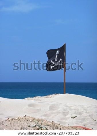 pirate flag on a beach - stock photo