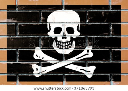Pirate flag painted on old brick wall texture background - stock photo