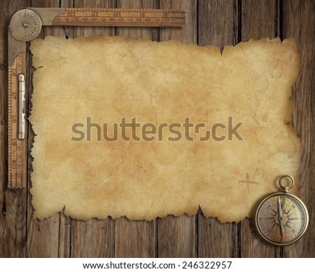 Pirates' old treasure map on wooden desk with compass and ruler - stock photo