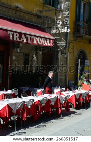 PISA, ITALY - MARCH 06,2015: Waiter of italian restaurant standing outdoor and waiting for customers. - stock photo