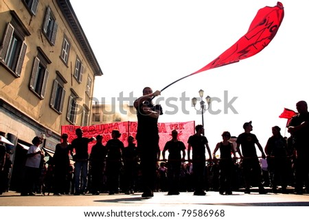 PISA, ITALY - MAY 6: Unidentified protester holds a red flag during the manifestation for the italian general strike on May 6,2011 in Pisa, Italy - stock photo