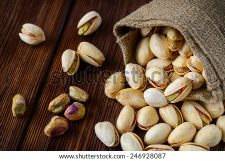 Pistachio nuts in a bag on an old wooden surface - stock photo