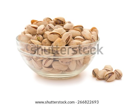 Pistachio nuts in a glass bowl on white with clipping path, side view - stock photo