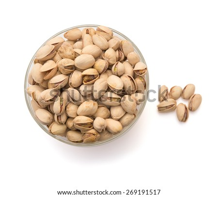 Pistachio nuts in a glass bowl on white with clipping path, top view - stock photo
