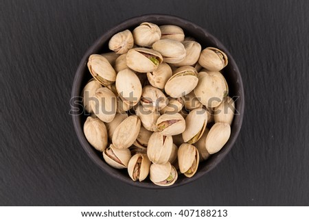Pistachio nuts in stone bowl on dark background - stock photo