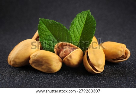 Pistachio nuts on a dark background - stock photo