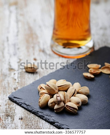 Pistachio nuts with beer on slate board. Selective focus - stock photo