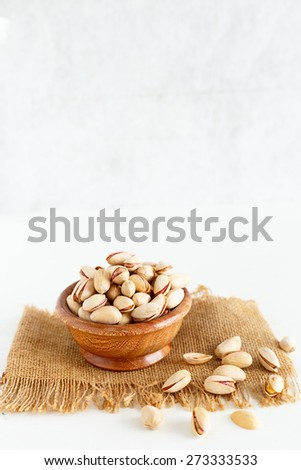Pistachio  Pistachio Nuts contained in a wooden bowl , some are scattered on an isolated white background - stock photo
