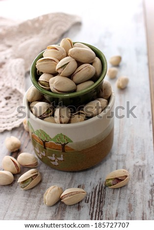 Pistachios in bowl on wooden - stock photo