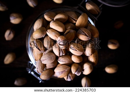 Pistachios in the glass jar from above, selective focus - stock photo