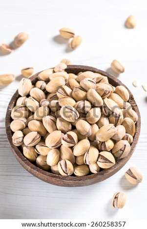 Pistachios in the wooden bowl on table,selective focus  - stock photo