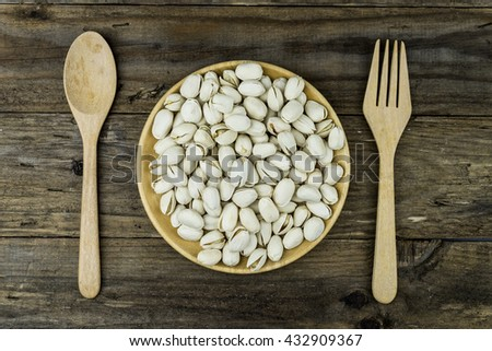 Pistachios nut and wooden fork and spoon on wooden plate on table or floor background - stock photo