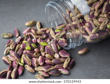 Pistachios of Bronte, Sicily, spilling from a jar - stock photo