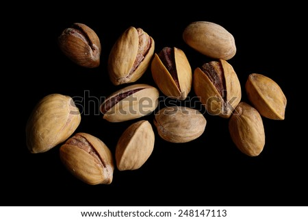 Pistachios on a black background. - stock photo