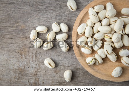 pistachios on a wooden plate on a wooden table. - stock photo