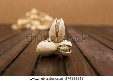 Pistachios on a wooden surface in the background slide of the shell. - stock photo