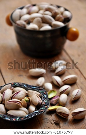 Pistachios on natural wooden table background - stock photo