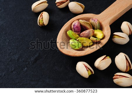 pistachios over dark slate background - stock photo