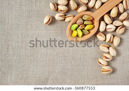 pistachios over ecru linen fabric background - stock photo