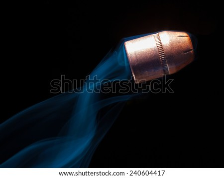 Pistol bullets on black with smoke trailing behind - stock photo