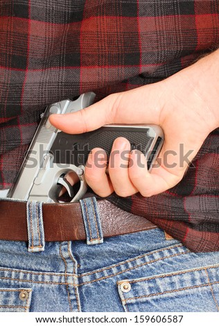 Pistol Concealed in a Man's Waistband  - stock photo