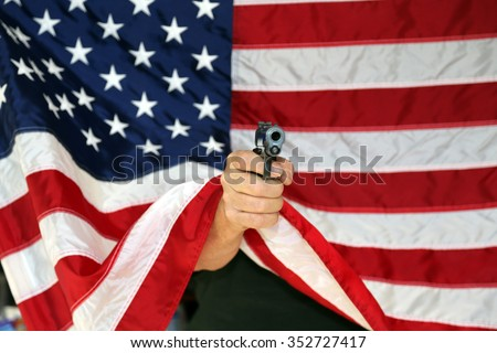 pistol pointed directly at the camera from behind an American flag. Represents Americas 2nd amendment rights to bare arms.  - stock photo