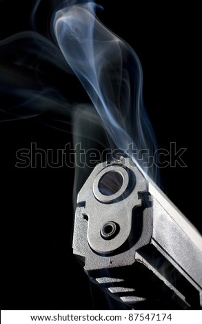 pistol that is smoking with a black background and muzzle lighting - stock photo