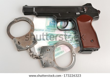 Pistol with handcuffs and money on gray background - stock photo