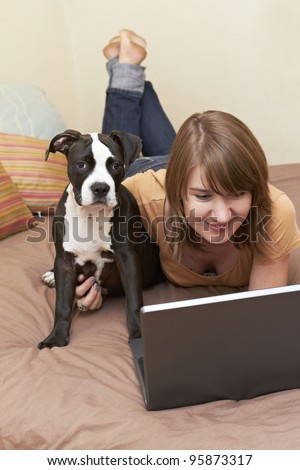 Pit Bull puppy sitting on bed with female owner looking at laptop - stock photo