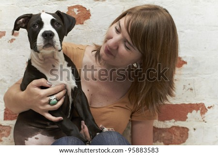 Pit Bull puppy with attractive young dog owner - stock photo