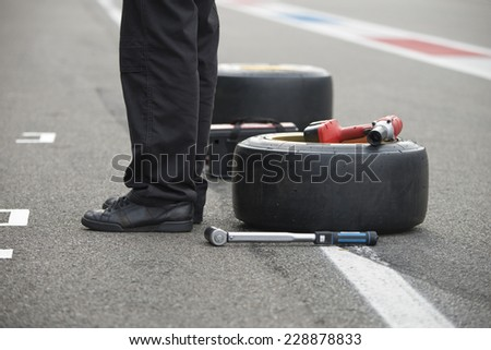 Pit crew mechanic waiting to get into achtion, with two replacement slick tires a power tool and a torque wrench lying on the asphalt of the pit lane behind him - stock photo