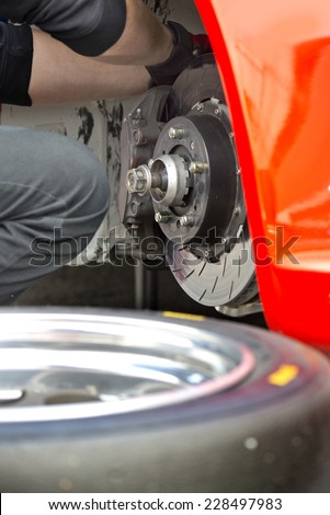 Pit crew mechanic working on the brake pads and brake disc of a red race car, with a spare tire in the foreground - stock photo