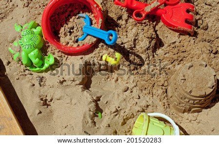 Pit sand with plastic toys - stock photo