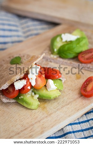 Pita bread with avocado and tomatoes on the wooden board - stock photo