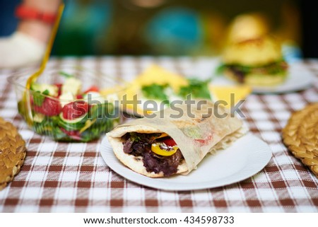 Pita sandwich with grilled meat with fresh salad food outdoor. Shallow depth of field. - stock photo