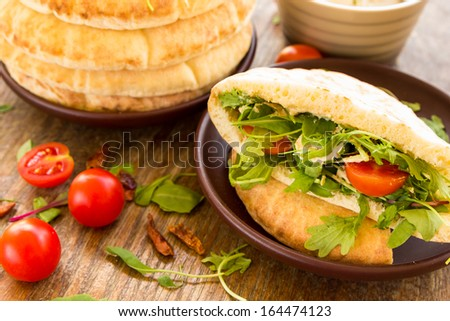 Pita with tomatos, cheese and salad mix on the clay plate - stock photo