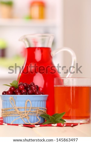 Pitcher and glass of cranberry juice with red cranberries on table - stock photo