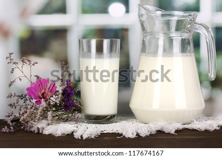 Pitcher and glass of milk on wooden table on window background - stock photo
