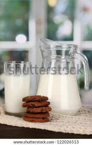 Pitcher and glass of milk with cookies on crewnecks knitwear on wooden table on window background - stock photo