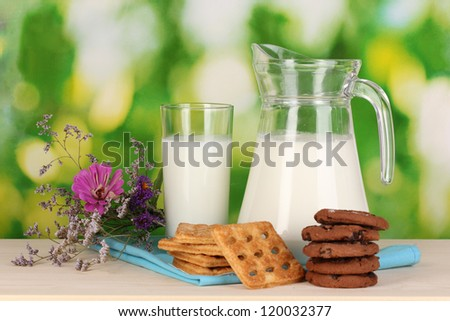 Pitcher and glass of milk with cookies on wooden table on natural background - stock photo