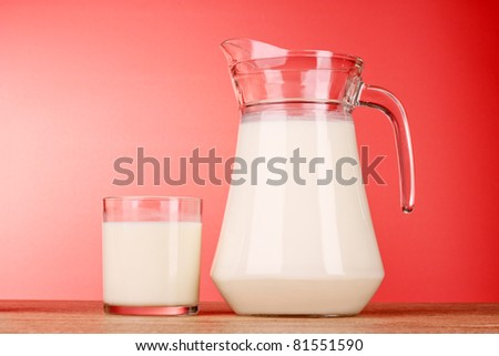Pitcher and Glass with milk on red background - stock photo